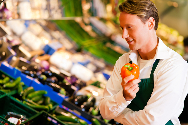 Grocery worker holding an orange pepper.