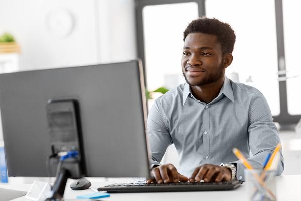 Man typing on a desktop computer keyboard.